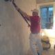 Slipning av spacklade väggar inför tapetsering.